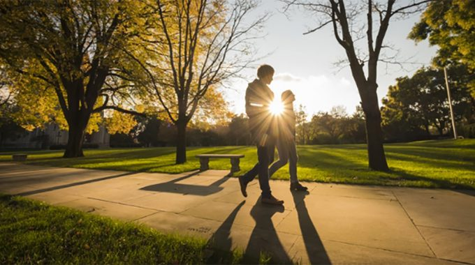 Image Of Two People Walking On A Campus.