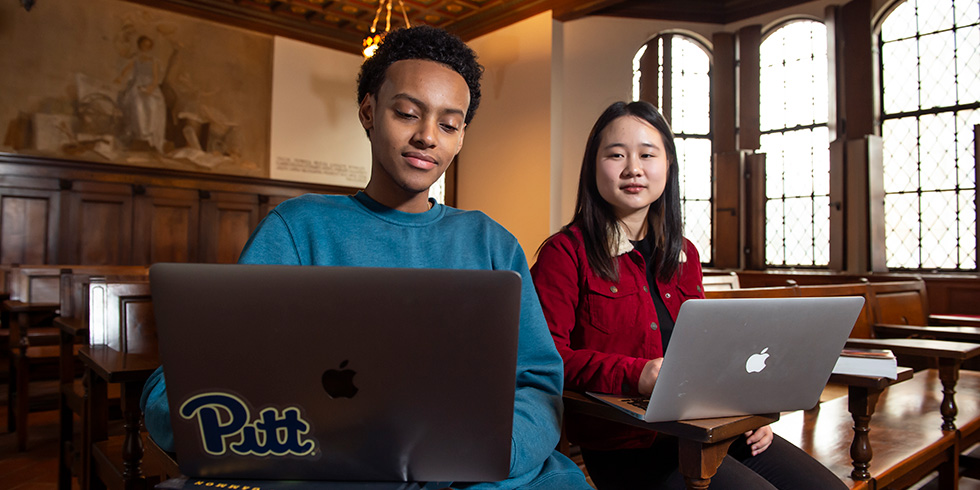Students working on laptops in a nationality room in the cathedral of Learning